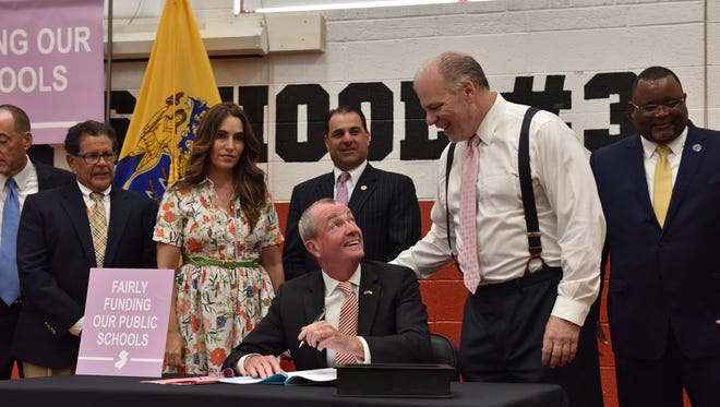New Jersey Governor Phil Murphy looks up at NJ Senate President Stephen Sweeney while signing the school funding legislation at Cliffside Park School No. 3 at Cliffside Park on Tuesday July 24, 2018.