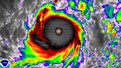 A color-enhanced satellite image shows Super Typhoon