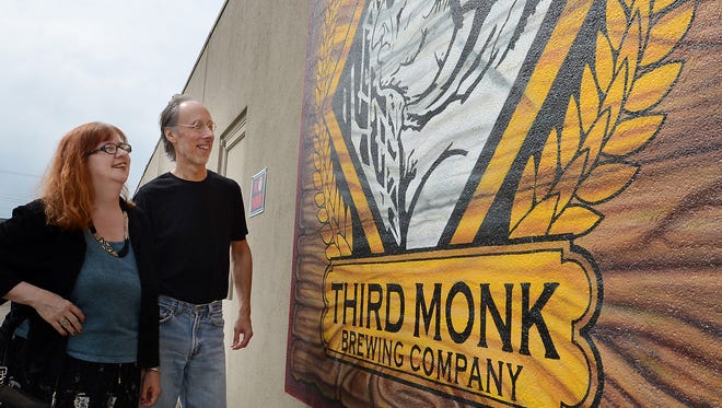 Josie Kearns, a member of the South Lyon Arts Commission, and Jeff Robinson, owner of Third Monk Brewery, take a look at the mural outside the brewery on Aug. 24. The pair, and others, value an arts survey in the city which gauged  interest in art in and around the city. Kearns and her husband, Joe Matuzak, worked on the survey. Robinson was a survey respondent. Art in Public Places is favored by respondents.