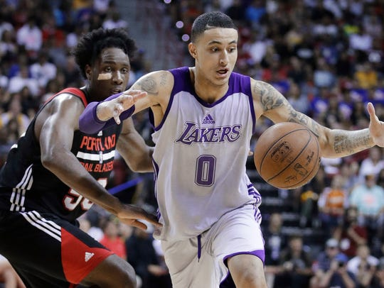 The Lakers' Kyle Kuzma, right, reaches for the ball