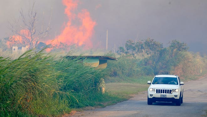 Flames from a grass fire reach into the air as a federal firefighter vehicle passes by on Turner Road on Nimitz Hill on April 5, 2014.