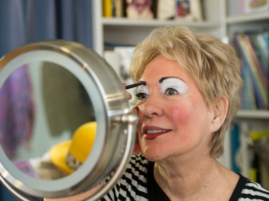 "Sandy ""Sunshine the Clown"" Johnson puts on her makeup."