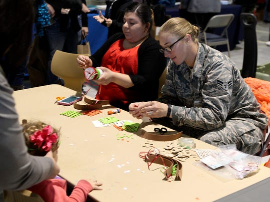 Airman 1st Class Laura New helps create a reindeer headband at the arts and crafts table during Saturday's Santa's Market at Goodfellow Air Force Base.