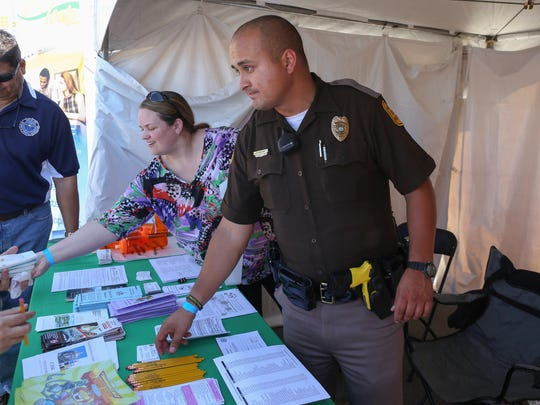 Mauricio Aguilera, an Iowa State trooper, walks the grounds around the Latino Heritage Festival on Saturday, Sept. 26, in Des Moines.