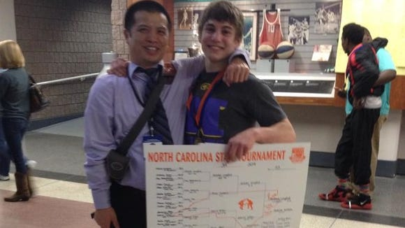 North Henderson wrestler Mitchel Langford, right, and coach Heang Uy at the 2014 NCHSAA tournament in Greensboro.