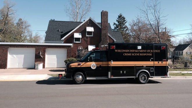 A Wisconsin state investigation vehicle is parked April 27, 2016, outside a home in Wisconsin Rapids, Wis., after police found a man and his two young children dead inside.