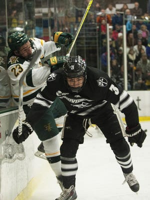 Friars defenseman John Gilmour (3) checks Catamount forward Rob Darrar (23) into the boards during the men's hockey game between the Providence Friars and the Vermont Catamounts at Gutterson Fieldhouse on Friday night in Burlington.