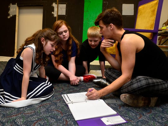 """Adrianne Purpura, left, Maddy Griessmer, center, and Jaiden Petrini talk about their parts with NDM Productions artistic director Zachary Dennis during rehearsal for their upcoming play """"Willy Wonka and the Chocolate Factory"""" on March 10."""
