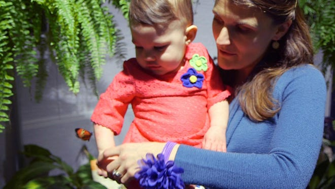 Mother and daughter examine the butterflies at ECHO.