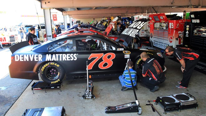 Crew members work on the No. 78 Furniture Row Chevrolet of Kurt Busch prior to Sunday's AAA 400 at Dover International Speedway.