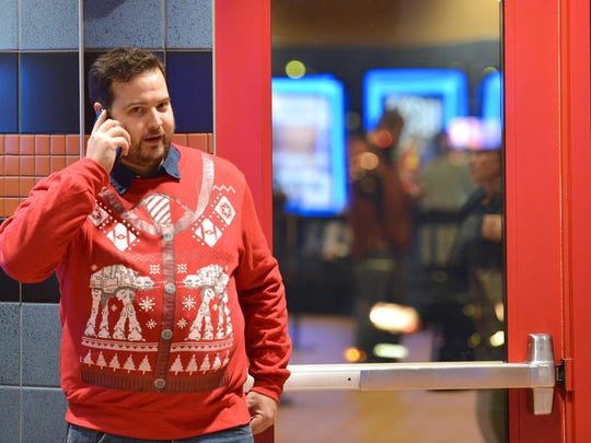 """Matt Wixson, 32, of Ferndale waits for friends to see the first showing of """"Star Wars: The Force Awakens"""" on Thursday at MJR Digital Cinemas in Troy. He is sporting a """"Star Wars"""" Christmas sweater."""