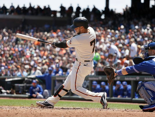 San Francisco Giants' Gregor Blanco hits an RBI double off Toronto Blue Jays starting pitcher Marcus Stroman in the second inning of their baseball game Wednesday, May 11, 2016, in San Francisco. At right is Blue Jays catcher Russell Martin. (AP Photo/Eric Risberg)