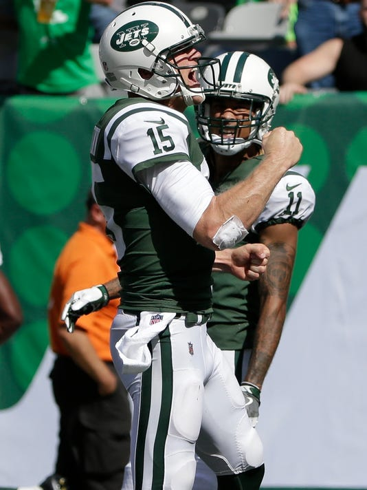 New York Jets quarterback Josh McCown (15) celebrates with teammate Robby Anderson (11) after they connected for a touchdown during the first half of an NFL football game against the Miami Dolphins, Sunday, Sept. 24, 2017, in East Rutherford, N.J. (AP Photo/Seth Wenig)