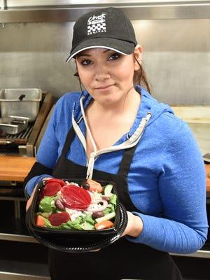 Pita House chef Lina Charara holds a Greek salad.