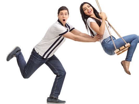 Delighted man pushing his girlfriend on a swing