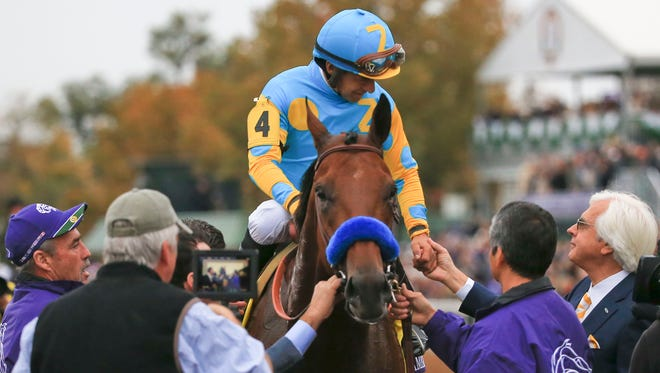 Victor Espinoza gets congratulations from trainer Bob Baffert after American Pharaoh won the Breeders' Cup Classic Saturday at Keeneland.