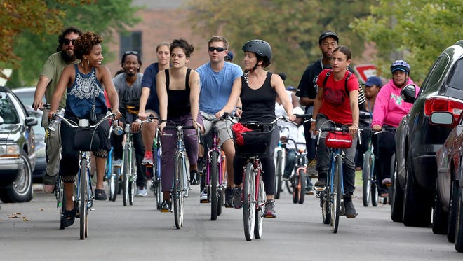 Cornetta Lane, far left, 28 from the Core City neighborhood in Detroit, leads a tour down Humboldt Street toward the first stop on a bike tour through of part of her neighborhood in Detroit on Saturday, Aug. 29, 2015.