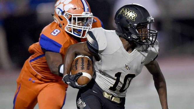 Northwest Rankin's Dee Baker runs through an arm tackle by Madison Central's Kobe Cole on Friday. MC won 35-24.