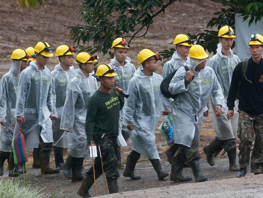 Rescuers walk toward the entrance of a cave complex where in Mae Sai, Chiang Rai province, northern Thailand.