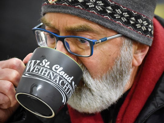 Jan Petersen sips a warm mug of Gluhwein, a red wine