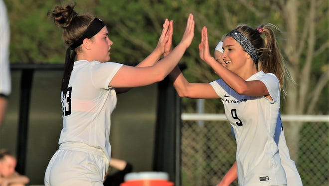 Plymouth senior Lexi White (9) high fives teammate Addisyn Lewis (13) after scoring one of her three goals Tuesday night against Livonia Churchill.