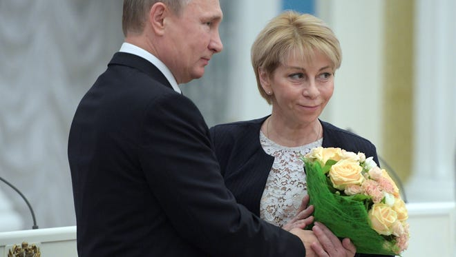 Russian President Vladimir Putin offers flowers to Elizaveta Glinka, executive director of the Fair Aid International Public Organization, during a ceremony to give out national awards for outstanding achievements in human rights and charity activity on Dec. 8, 2016. Charity activist Elizaveta Glinka or Dr. Liza was on board the Tu-154 travelling to Syria to celebrate the New Year with Russian troops. More than 60 members of the internationally-renowned Red Army Choir were on board a Russian military plane that crashed in the Black Sea on December 25, 2016, Russia's defence ministry said.  / AFP PHOTO / SPUTNIK / Alexei DruzhininALEXEI DRUZHININ/AFP/Getty Images ORIG FILE ID: AFP_JF1DU