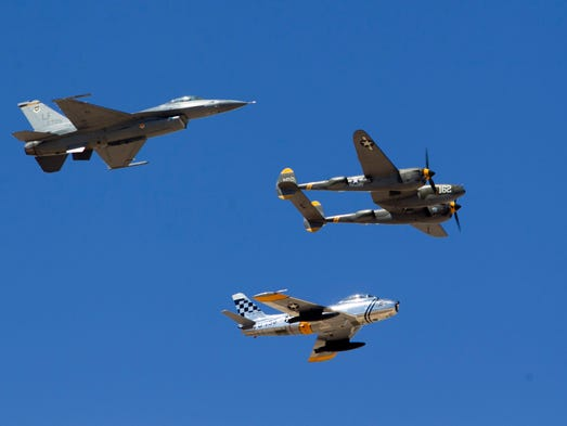"An F-16 flies with a F-86, a transonic jet fighter aircraft from the mid 20th century and a P-38, a World War II era fighter during  ""Luke Days 2014, Lightning in the Desert!"", an open house and air show at Luke Air Force Base in Glendale."