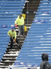 Stadium workers clear snow from the stands before the