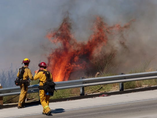 A fire crew knocks down flames along southbound I-15