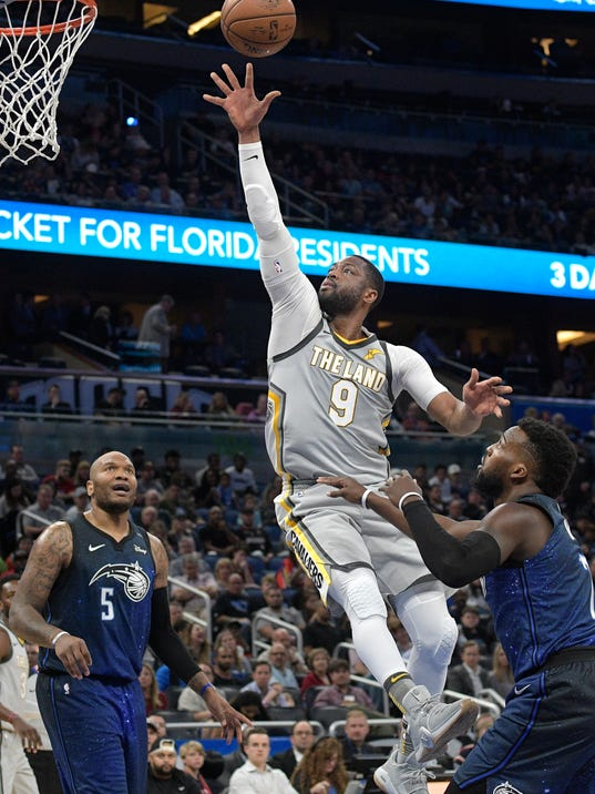 FILE - In this Feb. 6, 2018, file photo, Cleveland Cavaliers guard Dwyane Wade (9) puts up a shot between Orlando Magic forward Marreese Speights (5) and guard Shelvin Mack (7) during the first half of NBA basketball game, in Orlando, Fla. The Cavaliers dealt 36-year-old Wade to Miami for a second-round pick, Thursday, Feb. 8, 2018. (AP Photo/Phelan M. Ebenhack, File)
