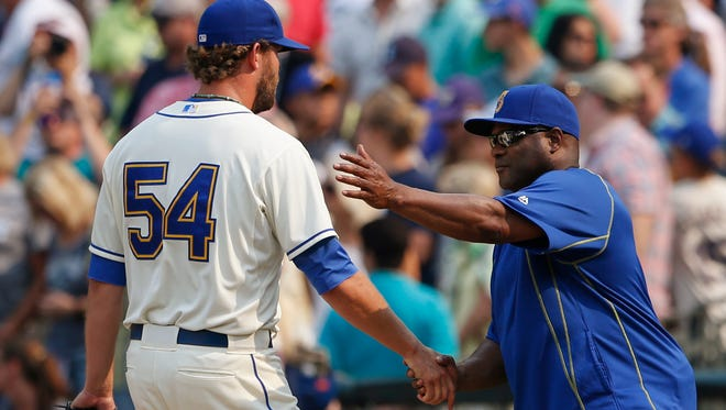 Seattle Mariners pitcher Tom Wilhelmsen shakes hands with manager Lloyd McClendon after Seattle's 8-6 victory against the Chicago White Sox in a baseball game, Sunday, Aug. 23, 2015, in Seattle.