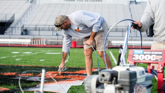 Steve Laughman paints in the orange on the stencil of the Nighthawks' logo, Thursday. The Hanover Public School District facilities crew spent three days and gallons of paint to prepare the Nighthawks' field ahead of their home opener.
