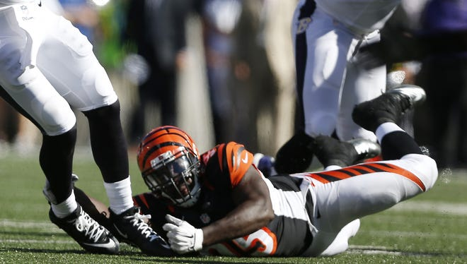 The Cincinnati Bengals defensive end Wallace Gilberry (95) trips up the Baltimore Ravens quarterback Joe Flacco (5) in the fourth quarter in Baltimore.