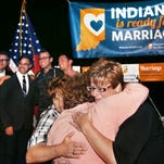 """IMPD Officer Teresa Welborn (left) and her wife, Beth Piette, (right) got a hug at the Hoosiers Unite for Marriage """"Love Wins"""" celebration in October."""