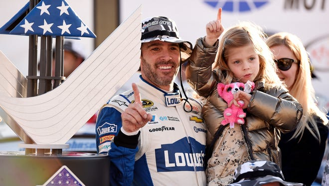 Jimmie Johnson celebrates with his daughter Genevieve after winning the Folds of Honor QuikTrip 500 Sunday at Atlanta Motor Speedway.