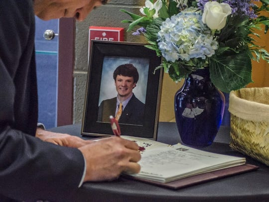 A visitor signs the condolence book during the funeral