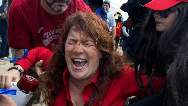 Jennifer Sterling, one of the organizers of the pro-Trump rally, reacts after getting hit with pepper spray by a counter-protester during a march in support of President Donald Trump, in Huntington Beach, Calif., on Saturday, March 25, 2017.