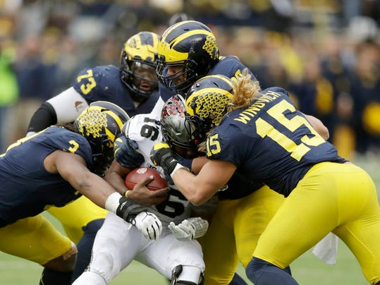 Ohio State quarterback J.T. Barrett (16) is sacked by Michigan defensive lineman Rashan Gary (3) and defensive lineman Chase Winovich (15) during the second half of an NCAA college football game, Saturday, Nov. 25, 2017, in Ann Arbor, Mich. Barrett did not return after the sack. (AP Photo/Carlos Osorio)