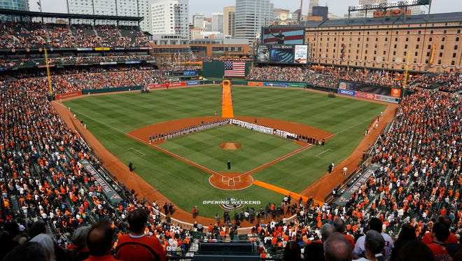 Members of the Minnesota Twins and Baltimore Orioles stand on the field during a rendition of the national anthem before an opening day baseball game, Thursday, March 29, 2018, in Baltimore.