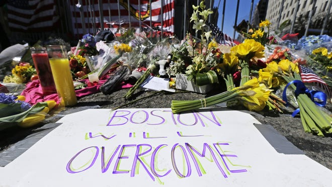 In this April 17, 2013, photograph, flowers and signs adorn a barrier two days after two explosions killed three and injured hundreds near the of finish line of the Boston Marathon at a makeshift memorial for victims and survivors of the bombing.