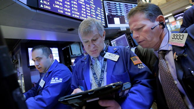 Traders Richard Newman, center, and Robert Charmak, right, work on the floor of the New York Stock Exchange, Tuesday, Nov. 22, 2016.