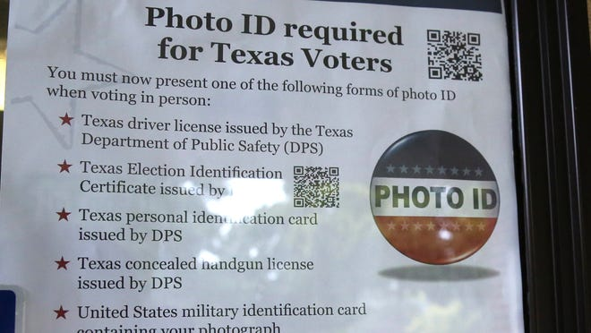 A sign warns of photo ID requirements at a polling location in Richardson, Texas, earlier this year.