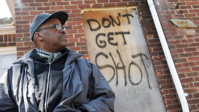 An empty home on Greensboro sports a warning to squatters. The Rev. Raynard Sims, a neighbor, always answers his door with a Glock.
