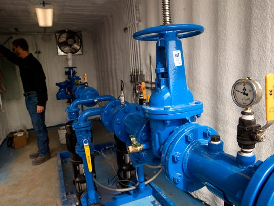 Clayton Harrison of Pillar Innovation works on the pump house on Oct. 18 in the Harvest Gold subdivision.
