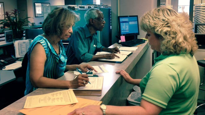 Mary L. Wardsworth (left) qualifies Friday afternoon to run for the District 4 seat on the Alexandria City Council, with assistance from Rapides Parish Clerk of Court Robin Hooter (right). Wardsworth beat the qualifying deadline with only minutes to spare. District F School Board member John Allen (center, background) looks over the qualifying list and found no one filed to run against him.
