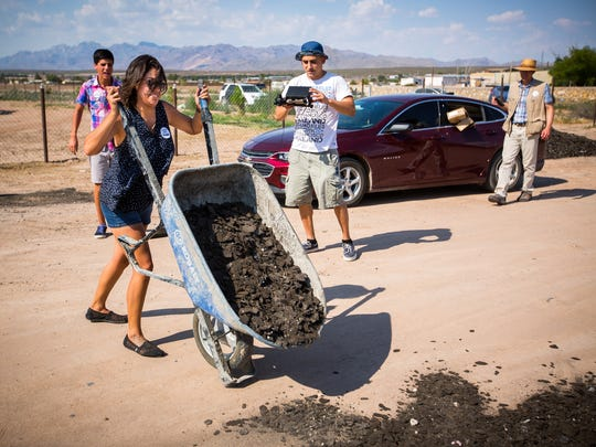 Johana Bencomo, a community organizer for New Mexico Comunidades en Acción y de Fe (CAFé), a Las Cruces-based nonprofit community organizing group that seeks to effect systemic change, dumps a load of recycled roofing shingle material on Cebolla Lane in Vado, Thursday, July 28, 2016.