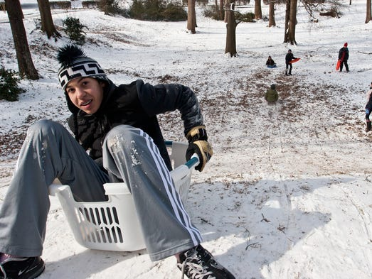 Grayson Gauthier prepares to slide down a snow-covered hill in a plastic laundry basket Thursday in Decatur, Ga. The rare snowfall left streets clogged with commuters and students taking a few days off.