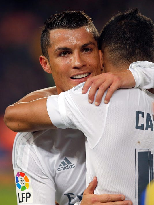 Real Madrid's Cristiano Ronaldo hugs teammate Casemiro, right, at the end of a Spanish La Liga soccer match between Barcelona and Real Madrid, dubbed 'el clasico', at the Camp Nou stadium in Barcelona, Spain, Saturday, April 2, 2016. Ronaldo scored the second goal in Real Madrid's 2-1 win. (AP Photo/Manu Fernandez)