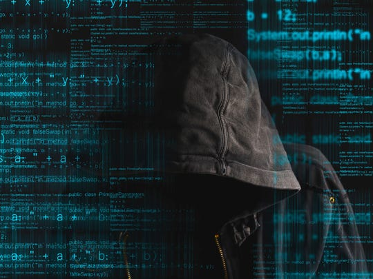 Faceless hooded anonymous computer hacker with programming code from monitor
