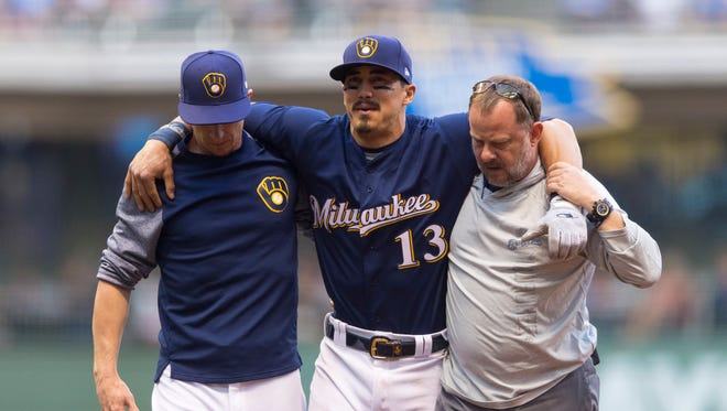 Brewers shortstop Tyler Saladino gets carried off the field after being injured during the third inning against the Cardinals on Tuesday.